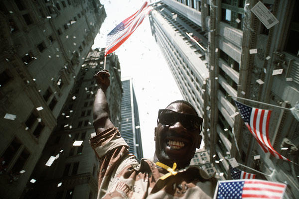 Army Pfc. White waves an American flag while the confetti and tickertape fall on the Welcome Home parade honoring the coalition forces of Desert Storm in New York, June 10, 1991. U.S. Air Force photo by Staff Sgt. Chuck Reger