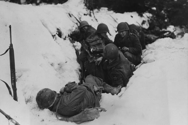 U.S. infantrymen of the 9th Infantry Regiment, 2nd Infantry Division, First U.S. Army, taking shelter from a German artillery barrage during the Battle of Heartbreak Crossroads in the Krinkelter woods, 14 Dec 1944. (Photo: US Army Signal Corps)