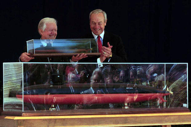 Former President and Navy submariner Jimmy Carter with a replica of the USS Jimmy Carter (SSN-23) given to him by Secretary of the Navy John H. Dalton at a naming ceremony on April 28, 1998. DoD photo by SSgt. Keith A. Stevenson, U.S. Marine Corps.