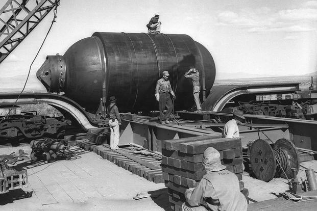 "At Alamagordo N.M., a Manhattan Project team assembles ""Jumbo"" or ""Big Brother"" prior to its detonation on July 16, 1945.  This detonation marked the first controlled atomic explosion and began the atomic age. (Los Alamos National Laboratory photo)"