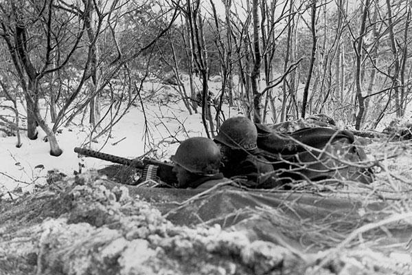 An American roadblock is set up with a 30-caliber heavy machine gun, and a tank destroyer is ready for action on Adolph Hitler Straase during the Battle of the Bulge. 1st Battalion, 157th Regiment, 45th Division (10 Dec 1944). Army Signal Corps Photo