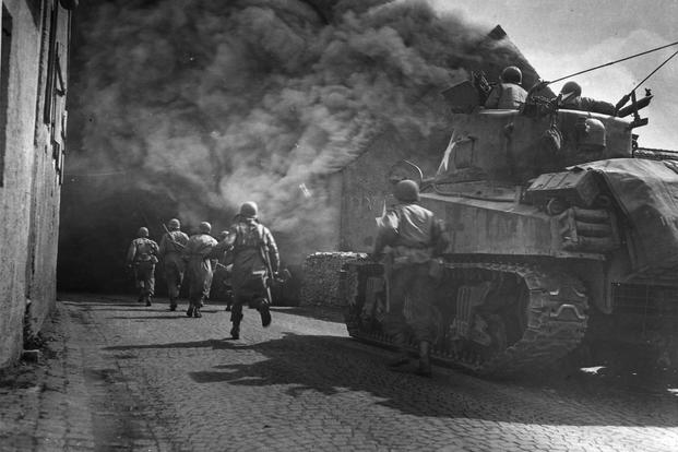 U.S. Third Army runs through smoke-filled streets in Wernberg, Germany. (Photo: National Archives)
