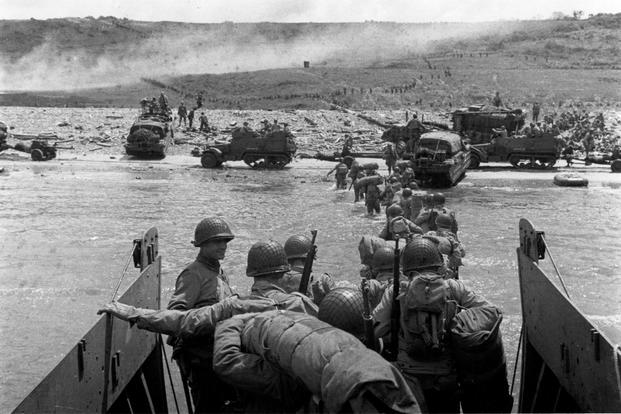 "U.S. troops wade ashore from a LCVP landing craft, off ""Omaha"" Beach, 6 June 1944. Note DUKWs and half-tracks at the water line, lines of men headed inland, and M1903 and M1 rifles carried by some of the troops leaving the landing craft. 6 June 1944"