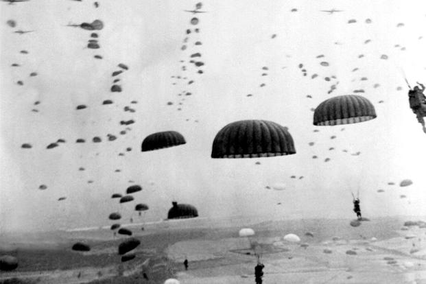 Parachutes open overhead as waves of paratroops land in Holland during operations by the 1st Allied Airborne Army. (Photo: National Archives)