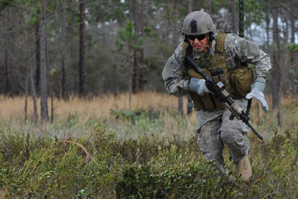 Special operations soldier running in a forest.