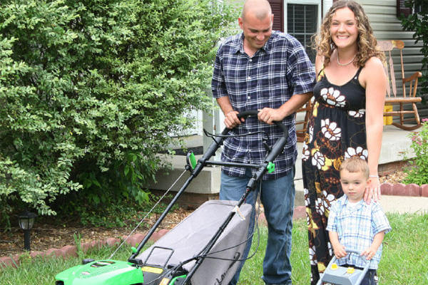 Military family mowing lawn.
