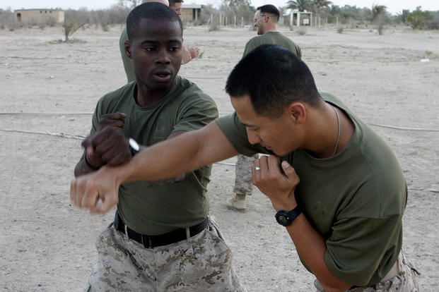 A Marine blocks a punch during a martial arts training session. (Marine Corps photo by Cpl Mike Escobar)
