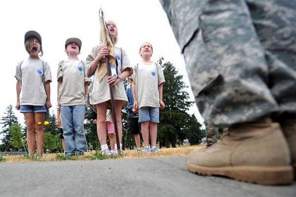 "Military children shout ""Fire in the hole!"" in response to their commander, Sgt. Russell Ho's call to attention at the 2010 deployment camp at Joint Base Lewis-McChord.  (Caption: Photo Credit: Ingrid Barrentine)"