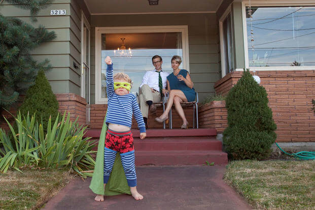 Young parents at home with son dressed as superhero