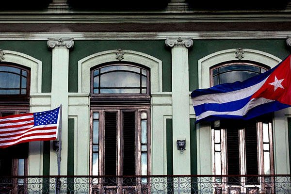 In this Jan. 19, 2015, file photo, a Cuban and American flag wave from the balcony of the Hotel Saratoga in Havana. Ramon Espinosa/AP