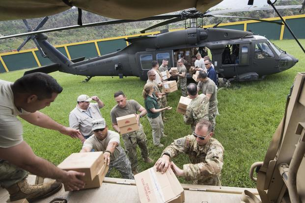 U.S. Army Lt. Gen. Jeff Buchanan, commander of Joint Task Force Puerto Rico, and soldiers from the Puerto Rico National Guard unload a UH-60 Blackhawk helicopter carrying critical supplies in Jayuya, Puerto Rico on Oct. 11, 2017. DoD photo