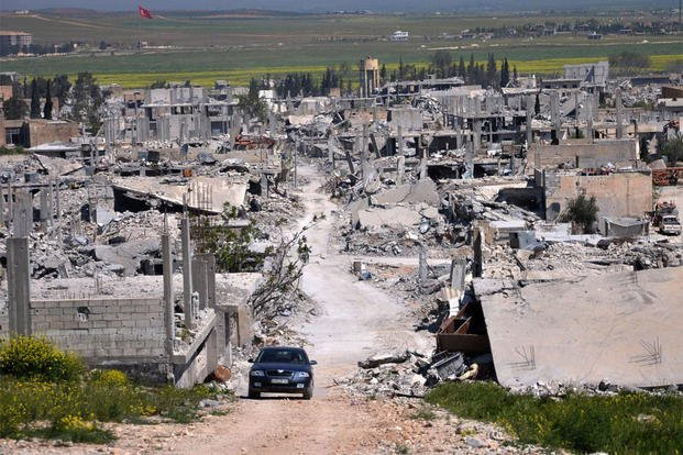 In this picture taken on Saturday, April 18, 2015, a car passes in an area that was destroyed during the battle between the U.S. backed Kurdish forces and the Islamic State fighters, in Kobani, north Syria. (AP Photo/Mehmet Shakir, File)