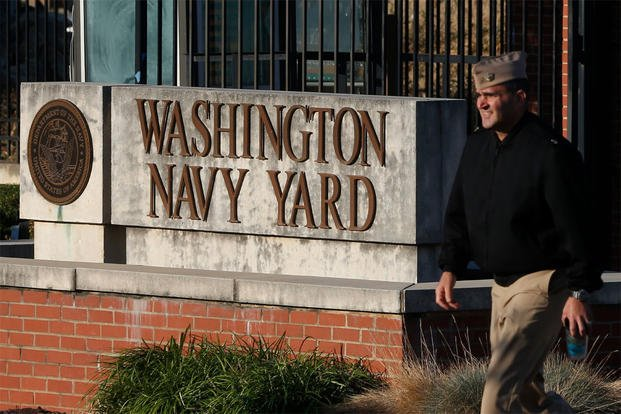 In this Sept. 19, 2013 file photo. military personnel walks past an entrance to the Washington Navy Yard in Washington. An official says shots have been reported in a building on the Washington Navy Yard campus. (AP Photo/Charles Dharapak, File)