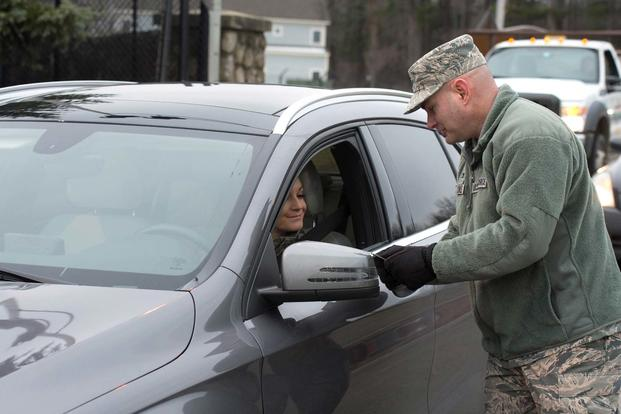FILE -- Col. David R. Dunklee, 66th Air Base Group commander, checks IDs at the Vandenberg Gate at Hanscom Air Force Base, March 23, 2016. (U.S. Air Force photo by Jerry Saslav)