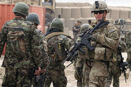 Afghan soldiers, left, walk past a U.S. Army soldier outside of a military base in Panjwai, Kandahar province south of Kabul, Afghanistan.
