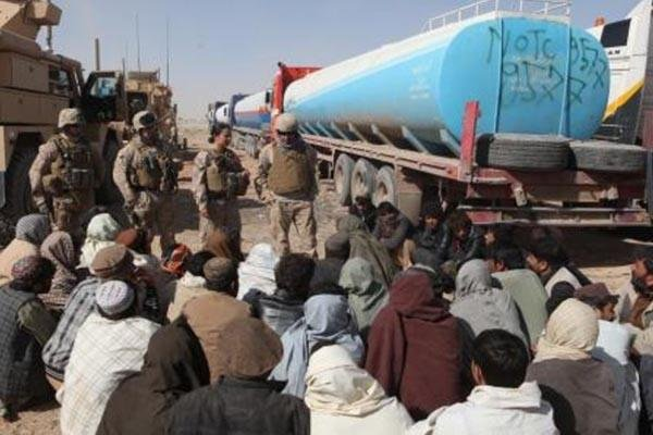 Marine First Lt. Mariela Pena, center, speaks through an interpreter to Afghan truck drivers near Camp Leatherneck in March 2012. The Afghan army may have broken the economic embargo against Iran by buying Iranian oil with American aid. John Jackson/DVIDS