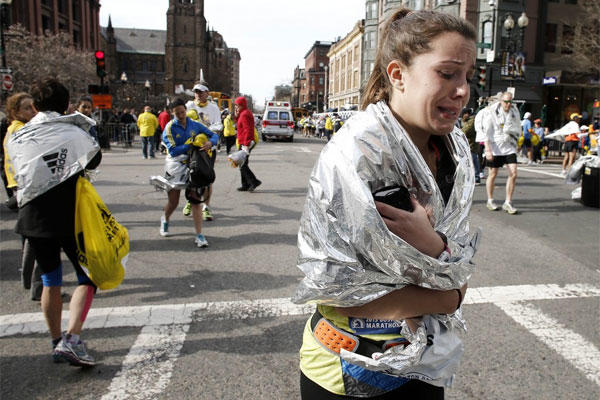 A Boston Marathon runner leaves the course crying near Copley Square following an explosion at the finish line in Boston on Monday, April 15, 2013.