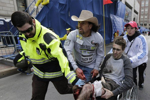 An emergency responder and volunteers, including Carlos Arredondo in the cowboy hat, push Jeff Bauman in a wheel chair after he was injured in an explosion near the finish line of the Boston Marathon Monday, April 15, 2013.