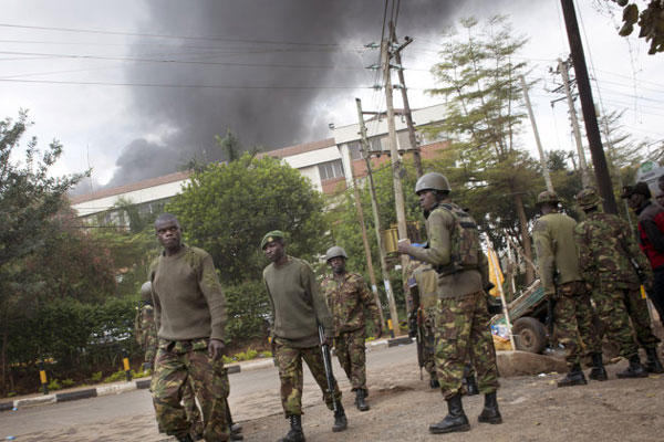 Kenyan security forces walk back from the Westgate Mall as black smoke billows above, following large explosions and heavy gunfire, in Nairobi, Kenya Monday, Sept. 23, 2013.