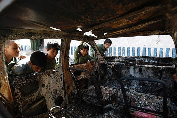 This May 27, 2014, file photo shows Yemeni boys looking at a vehicle destroyed during a police raid on an al-Qaida militants' hideout in the Arhab region, north of Sanaa, Yemen, which resulted in the death of five militants and six soldiers. Hani Mohammed