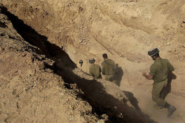 FILE - In this Sunday, Oct. 13, 2013 file photo, Israeli soldiers enter a tunnel discovered near the Israel Gaza border (AP Photo/Tsafrir Abayov, File)