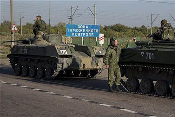 Russian soldiers and armored vehicles gather at a railroad crossing about 30 kilometers (19 miles) from the Ukrainian border on Friday, Aug. 15, 2014. Pavel Golovkin/AP