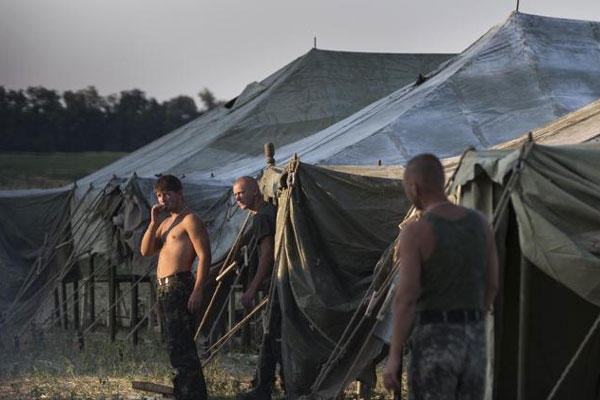 Ukrainian soldiers spend their time at a tent camp as the sun sets over the scene near the Russia-Ukraine border just outside the village of Gukovo, Rostov-on-Don region Monday, Aug. 4, 2014. (AP Photo/Alexander Zemlianichenko)