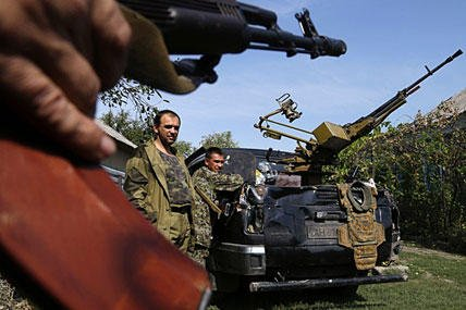 Pro-Russian rebels stand next to their car with a heavy machine gun in Donetsk, eastern Ukraine, Sunday, Sept. 7, 2014. Sergei Grits/AP