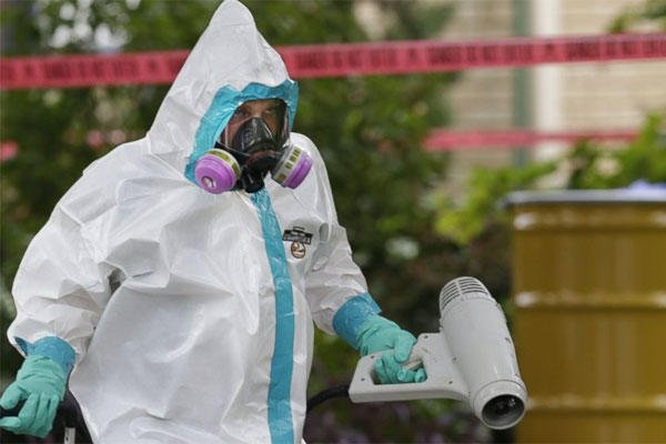 A hazmat worker clean outside the apartment building of a hospital worker, Sunday, Oct. 12, 2014, in Dallas. (LM Otero/AP Photo)