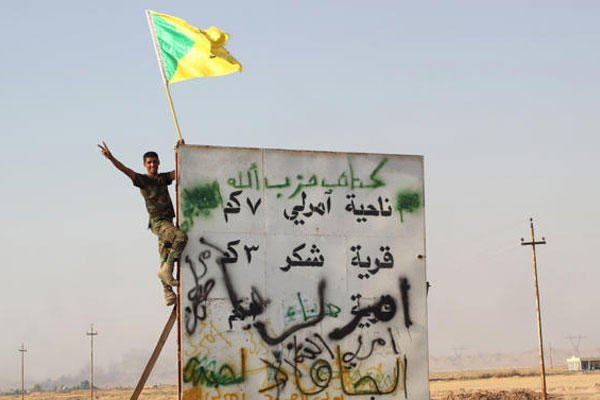 In this Monday, Sept. 1, 2014 file photo, a member of Iraq's Hezbollah Brigade holds their flag during an operation outside Amirli, some 105 miles (170 kilometers) north of Baghdad, Iraq. (AP Photo, File)