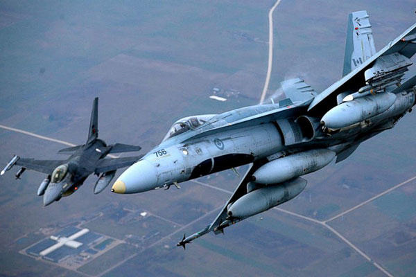 A Portuguese military fighter jet, left, and a Canadian military fighter jet participating in NATO's Baltic Air Policing Mission operate in Lithuanian airspace, Thursday, Nov. 20, 2014. Mindaugas Kulbis/AP
