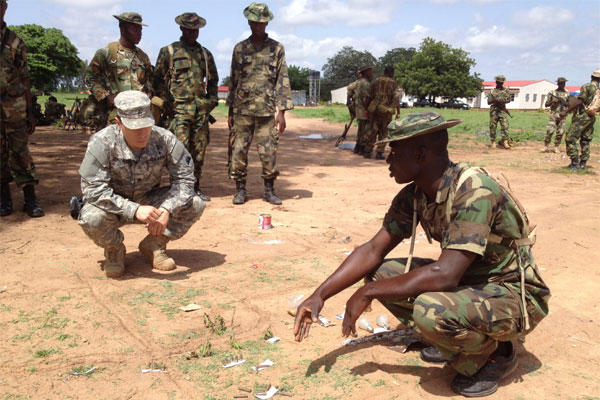 A Special Forces Soldier from Los Alamitos-based Special Operations Detachment-U.S. Northern Command and Company A, 5th Battalion, 19th Special Forces Group (Airborne), reviews a sand table map with a Nigerian soldier. (Photo by Courtesy photo)