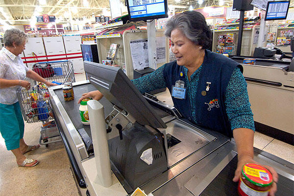A commissary cashier checks groceries at Tinker Air Force Base, Oklahoma. Commissary cashiers are federal employees on the GS system. (U.S. Air Force/Margo Wright)