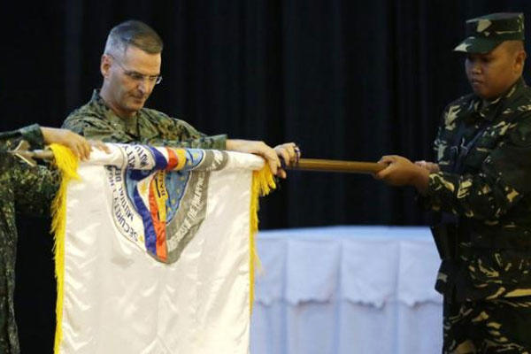 "Co-chairs of the joint U.S.-Philippines ""Balikatan 2015"" exercise unfurl the Balikatan flag during the opening ceremony Monday, April 20, 2015 at Camp Aguinaldo at Quezon city, northeast of Manila, Philippines. (AP Photo/Bullit Marquez)"