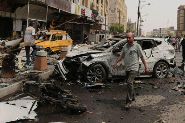 Civilians and security forces inspect the scene of a car bomb explosion on May 9 in Baghdad. (Photo: Karim Kadim/AP)