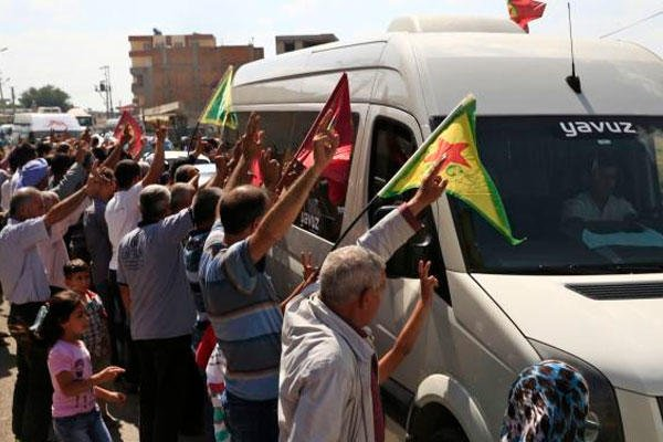 Kurdish people waving flags as the convoy carrying the body of U.S. citizen Keith Broomfield is driven by through Suruc, on the Turkey-Syria border, Thursday, June 11, 2015. (AP Photo/Lefteris Pitarakis)