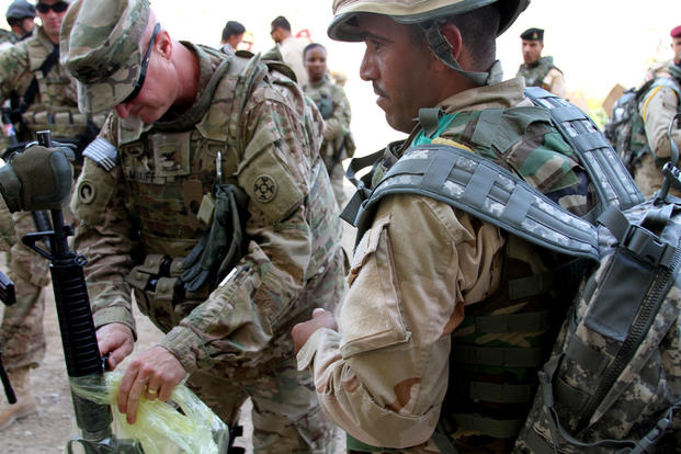 Col. Michael Midkiff helps an Iraqi soldier unwrap an M16A2 rifle he received at Camp Taji, Iraq. (Photo by Capt. A. Sean Taylor, 310th A&A, CJTF-OIR Public Affairs)