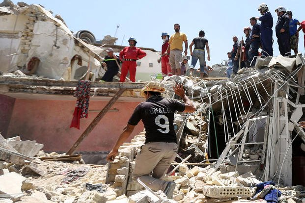 Iraqi security forces search for survivors after a fighter jet accidentally dropped a bomb over a Baghdad neighborhood on Monday, July 6, 2015. Hadi Mizban/AP