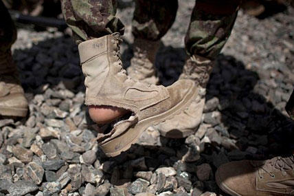 An Afghan National Army soldier shows his boot, which is falling apart after only two months.