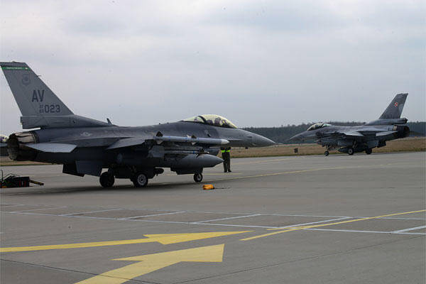 A Polish F-16 Fighting Falcon taxis past a 555th Fighter Squadron F-16 before a training mission, March 18, 2014, at Lask Air Base, Poland.