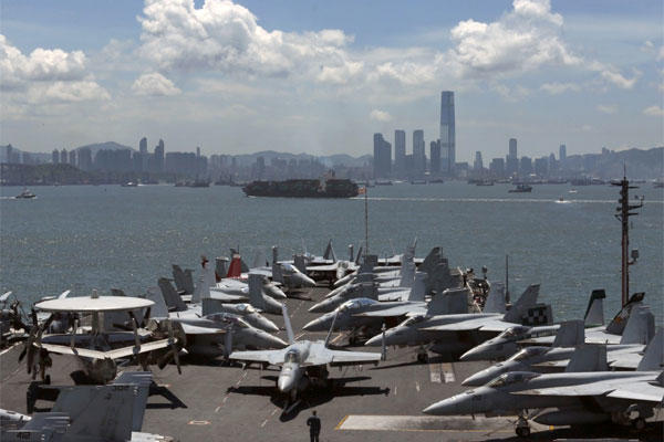 A U.S. Marine patrols beside the F/A-18 fighter jets on the deck of the aircraft carrier USS George Washington in the Hong Kong water for a port call Tuesday, July 10, 2012. (AP Photo/Kin Cheung)