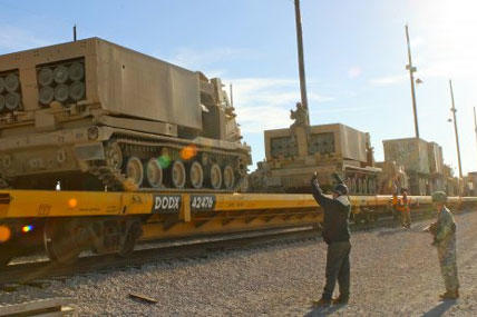 Soldiers from 2nd Battalion, 20th Field Artillery Regiment, task Force Pegasus, work to load multiple launch rocket systems onto flat train cars at the Fort Hood railhead, Jan. 30. (U.S. Army photo by Sgt. Garett Hernandez)