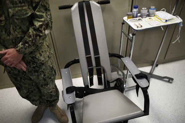 A US navy nurse stands next to a chair with restraints, used for force-feeding during a tour of the detainee hospital at Guantánamo Bay naval base in Cuba. (Charles Dharapak/AP)