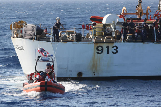 In this photo taken in the Florida Straits on May 17, 2015, members of the U.S. Coast Guard Cutter Charles David Jr, foreground, leaving the USCG cutter Mohawk with six Cuban migrants. (AP Photo/Tony Winton)