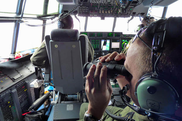 In this image, Petty Officer 1st Class Mike Crosby scans the surface of the Atlantic Ocean through his binoculars while in the cockpit of a Coast Guard HC-130J, July 28, 2015. (Senior Chief Petty Officer Sarah B. Foster/U.S. Coast Guard via AP)