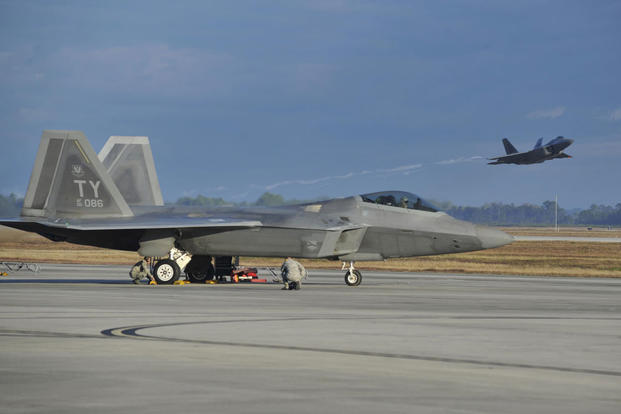 An F-22 Raptor from Tyndall Air Force Base, Fla., sits on the flightline while a Raptor launches from the Tyndall runway Dec. 10, 2015, during Checkered Flag 16-1. (Photo: Senior Airman Sergio A. Gamboa)
