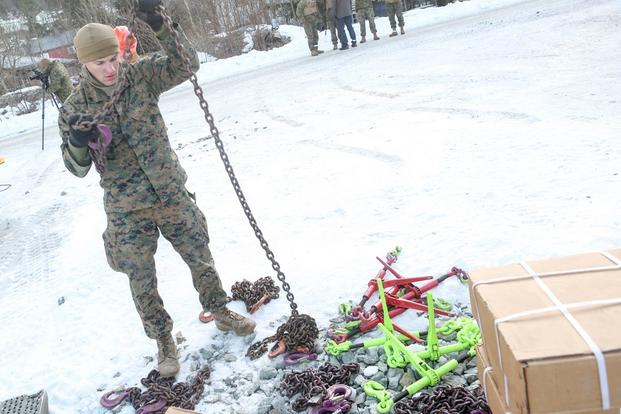 A Marine with 2nd Marine Expeditionary Brigade prepares the tie down chains shortly before transporting multiple vehicles by rail at Hell Station in Hell, Norway Feb. 12, 2016. (Photo: Cpl. Dalton Precht)