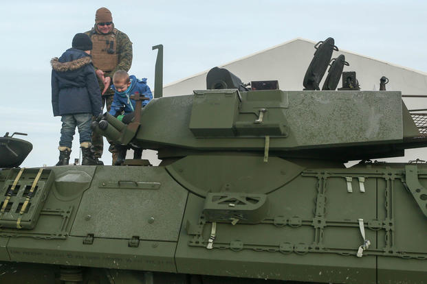 A Marine with 2nd Marine Expeditionary Brigade shows local children around a light armored vehicle at Hell Station in Hell, Norway, Feb. 12. (Photo: Cpl. Dalton Precht)