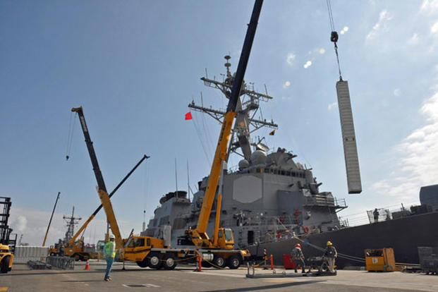 A vertical launch missile canister is loaded onto a guided missile destroyer at the Naval Weapons Station Seal Beach wharf. (Photo: U.S. Navy)
