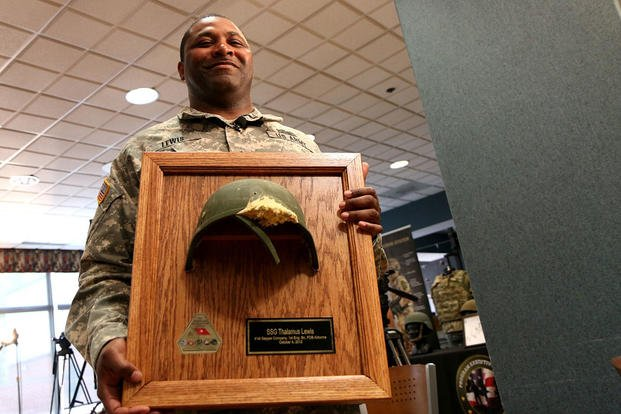 Army Staff Sgt. Thalamus Lewis received the helmet that saved his life in Afghanistan at an April 19 ceremony at Fort Belvoir, Va. The enemy rifle round struck the right side of his Advanced Combat Helmet and blew out the front. Matthew Cox/Military.com